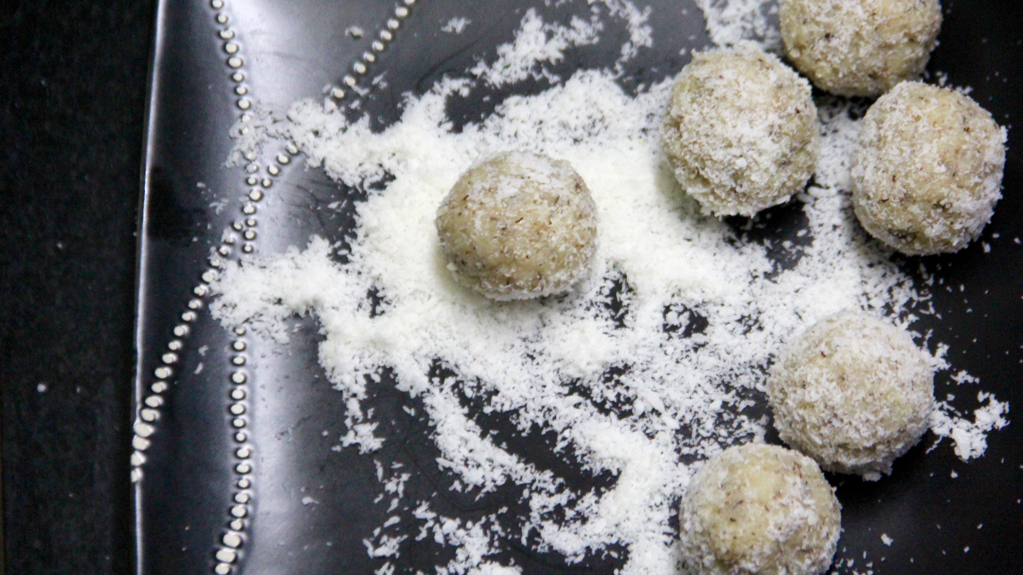 Rolling prepared ladoo over desiccated coconut